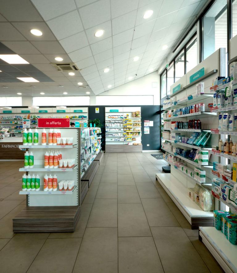 Vista interna della farmacia Campofiorenzo di Casatenovo LC progetto e realizzazione Clou. Questa farmacia di concorso si sviluppa sull'essenzialità dell'area vendita in cui emerge fortemente il carattere industriale dell'edificio.